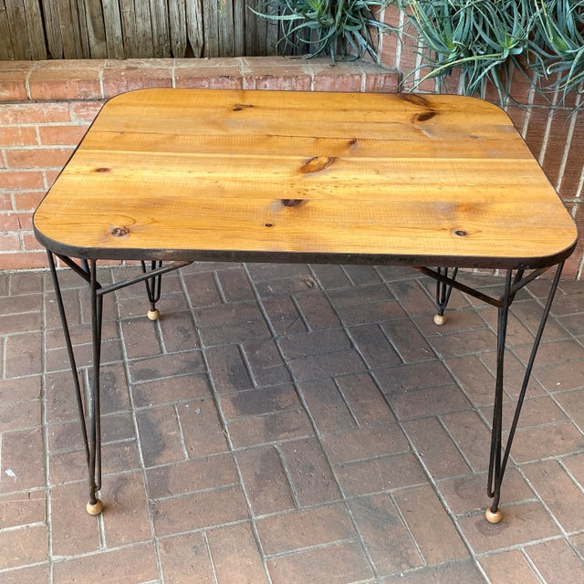 This 1950s solid wood and hairpin iron leg table (*note the wood ball feet) epitomizes that certain mid-century modern...