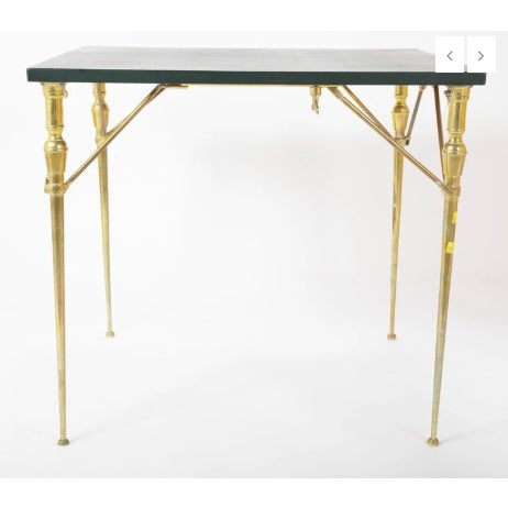 A leather top table with gold Fleur-de-Lis tooling. The base is well cast and polished brass inspired by neoclassic...