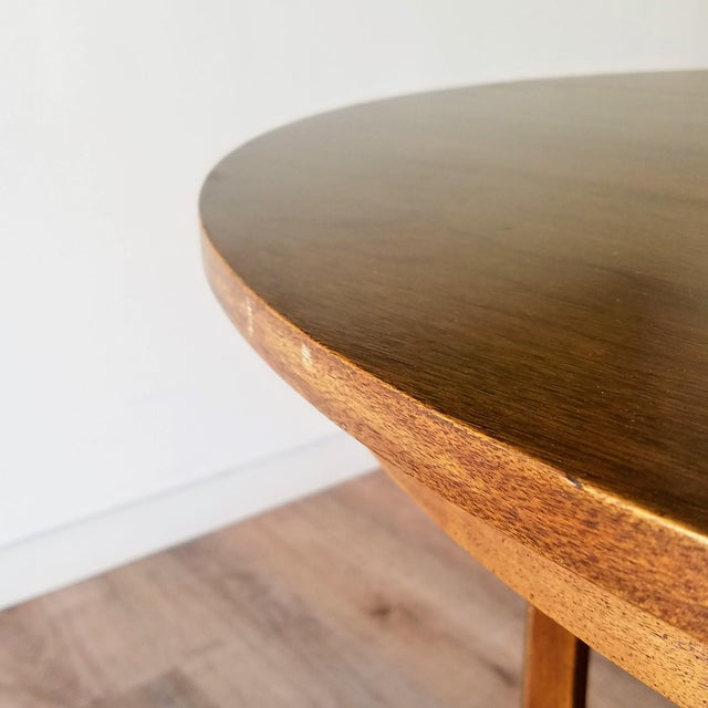 A round walnut dining table made by Broyhill for their Brasilia collection in the 1960s. The table features the iconic...