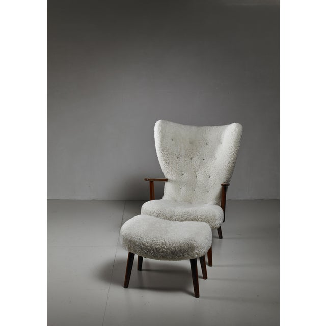 A high wingback lounge chair and ottoman, with a white sheepskin buttoned upholstery. These items were designed by Acton...