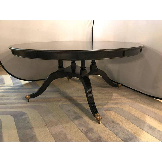 Monumental Hollywood Regency Style custom-made ebony circular extending dining table. This finely crafted one of a kind...