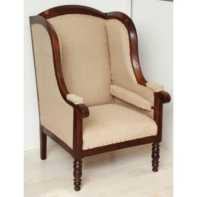 An unusually large walnut framed upholstered wing chair, France, circa 1810.