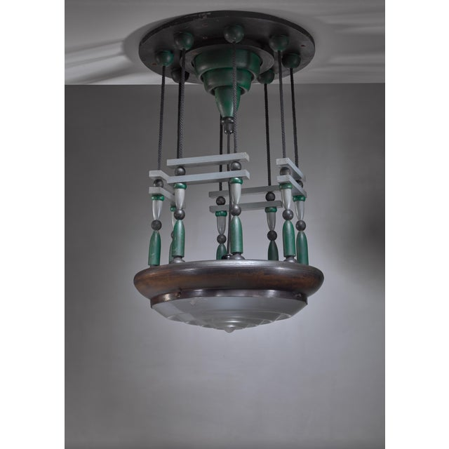 An early Modernist / De Stijl pendant lamp from Belgium. The lamp is made of black and green wood with a nickel plated...
