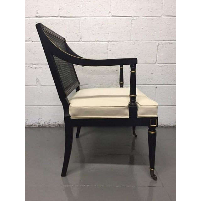 Pair of Maison Jansen style cane armchairs. Black lacquered, caned back with gold trim and original brass casters.