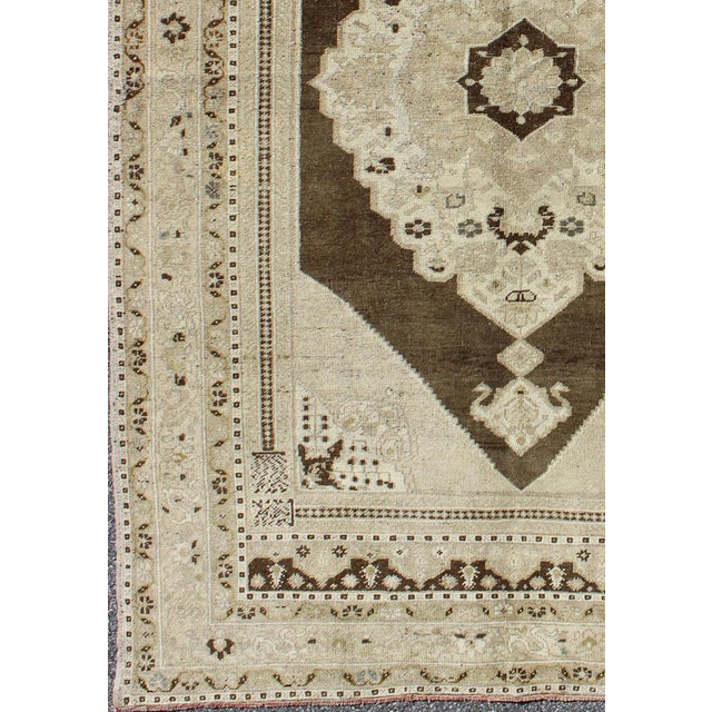 This vintage Turkish Oushak carpet (circa mid-20th century) features a central medallion design, as well as patterns of...
