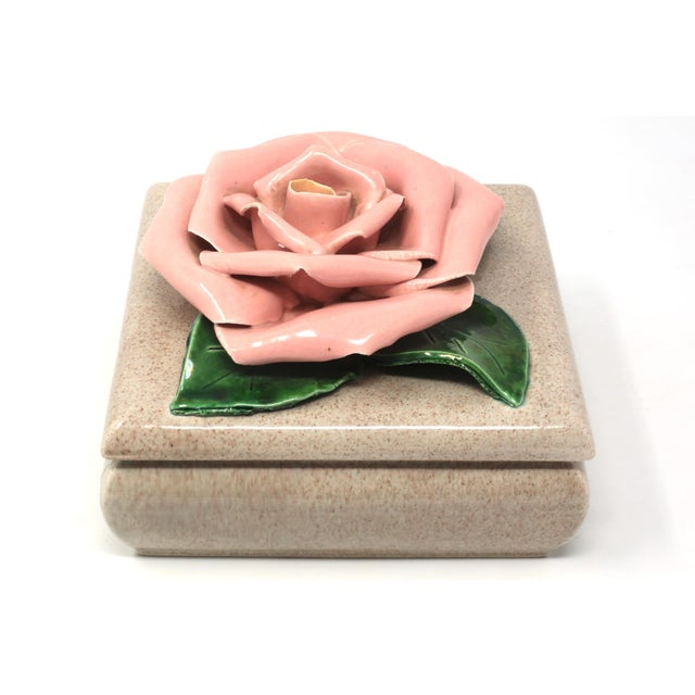 A vintage 1971, ceramic square-shaped dish with a beige speckled finish and large, sculpted camellia bloom on the lid....