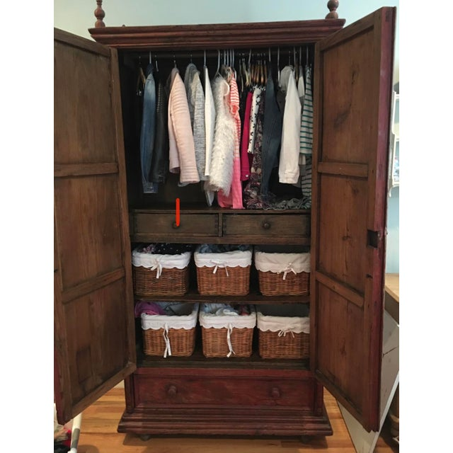 Rustic, farmhouse armoire with plenty of storage. Interior has a hanging bar, two drawers and a bottom drawer. There is an...