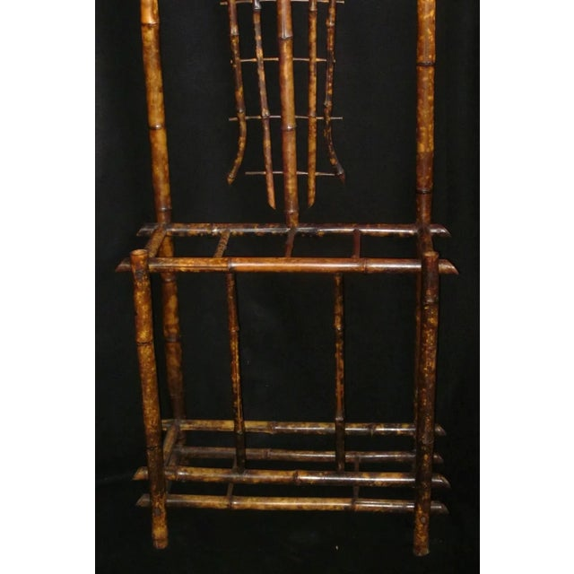 This is a 19th century Art Nouveau bamboo woven back hall tree with beveled shield mirror and nouveau tile. It is in great...