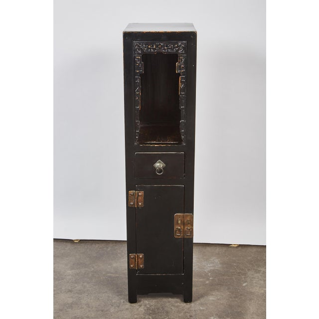 A one of a kind late 18th century Chinese, Qing Dynasty black lacquer one door, one drawer tall tea table that has...