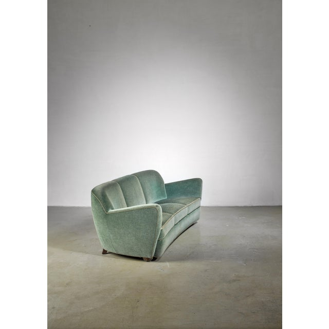 A three-seater sofa attributed to Danish designer Georg Kofoed. The sofa stands on stained beech legs and is upholstered...