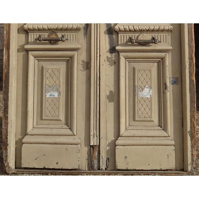 """A pair of antique doors from South America with ornate carved details and a transom. Doors approximately 48 """" wide..."""