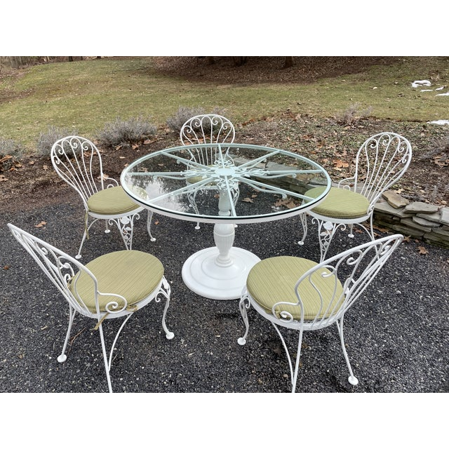 Classic patio dining table and chairs by Woodard having round table with center pedestal and pretty flower and leaf...