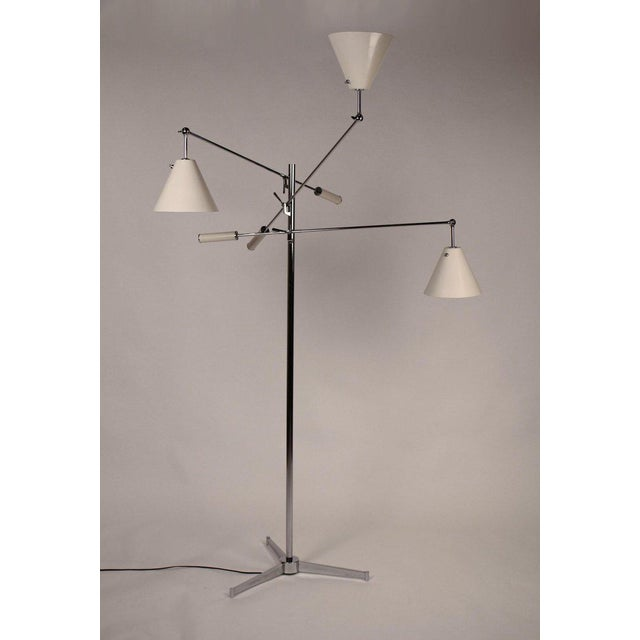 Early Arredoluce floor lamp in an off-white finish with tripod base designed by Angelo Lelii. Fully rewired and ready for...