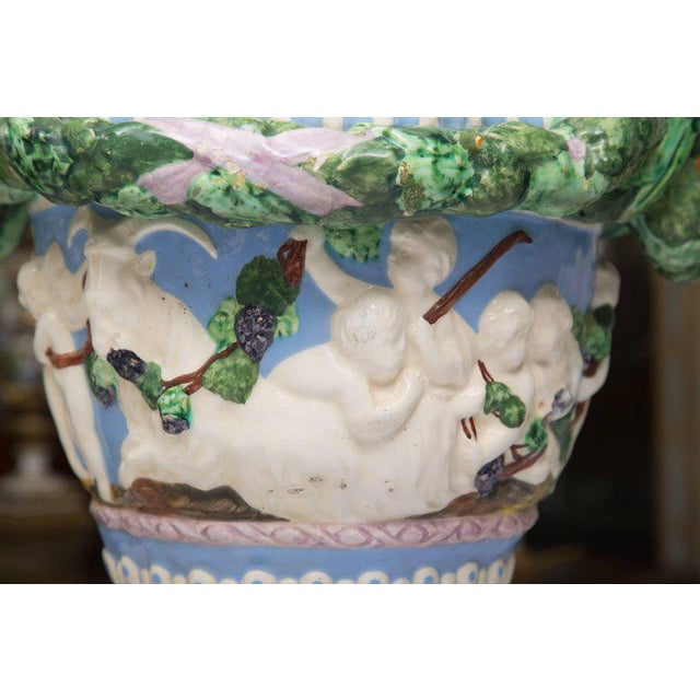 This is an Italian glazed Della Robbia lidded urn and hand-painted in Classic colors of the genre with a bold green wreath...