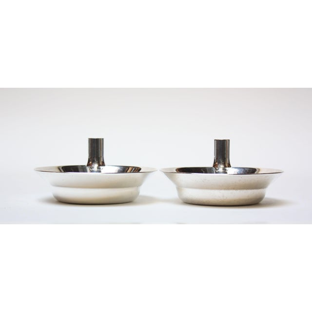 Pair of silver-plate 'saucer' candle holders designed by Jens H Quistgaard and produced by Dansk Designs Copenhagen. The...