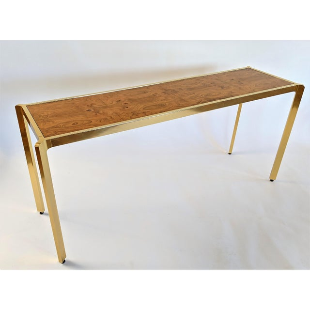 Brass console table with bookmatched Burlwood top. In excellent condition. Brass is bright and shiny. Wood grain top is...