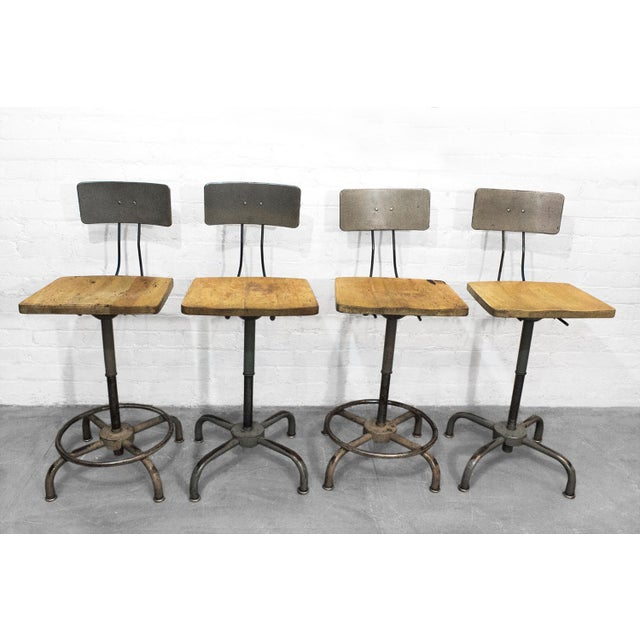 Very rare set of four Industrial stools from Adjusto Equipment Company of Ohio. Maple seats with steel backrests. Two are...