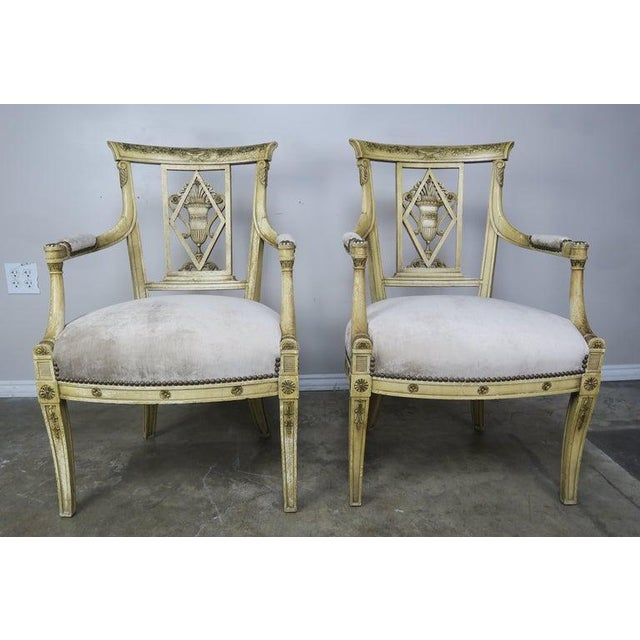 Pair of 1930's Italian Neoclassical painted armchairs. The armchairs are beautifully detailed with handled urns filled...