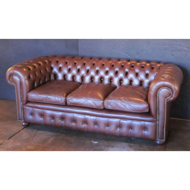 A fine English Chesterfield sofa in vintage brown leather featuring button-tufted back and arms, three soft leather fitted...