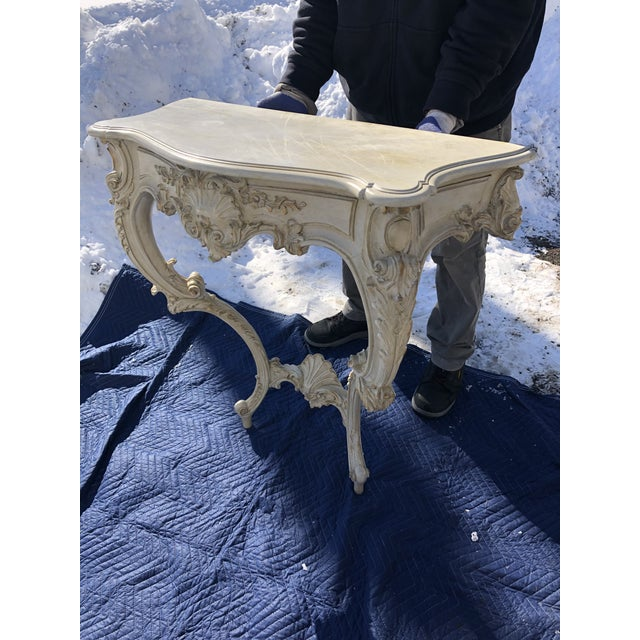 A gorgeous ivory painted parcel-gilt carved wood console table having an overhanging serpentine top above a front frieze...
