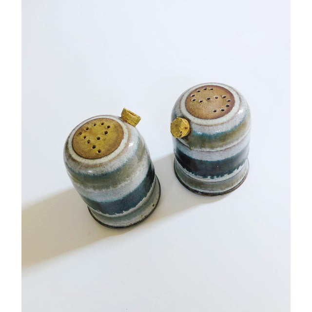A wonderful set of vintage stoneware studio pottery salt and pepper shakers. Nice neutral gray color base with stripes of...