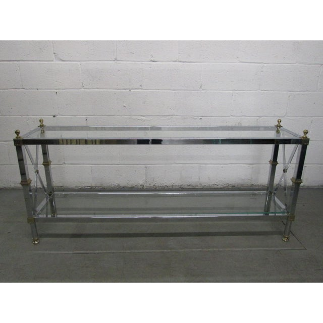 French Style Console Table. Console table has X stretcher to the sides, with brass and chrome frame. Glass on top and...