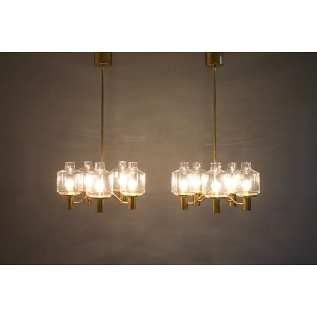 Nice pair of Hans Arne Jakobsson Brass and Glass Chandeliers made by AB Markaryd, Sweden, 1960s. Five clear glasses per...