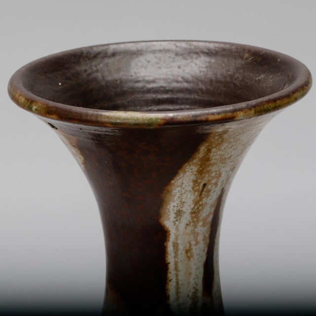Ceramic vase signed by Belgian artist Maurice Pitot has a drip glaze in earth tones with slender neck and applied,...