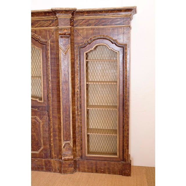 Fine Italian parcel-gilt and faux bois grain painted bookcase in three parts with shelves behind metal mesh doors and...
