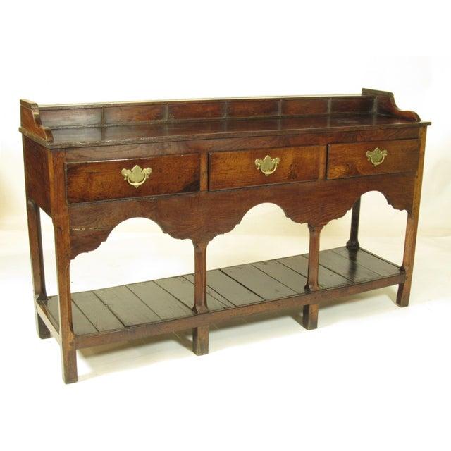 An 18th-C. Welsh George II elm server with three frieze drawers, a lower shelf, original brass and original rich patina....