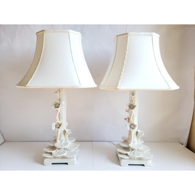 """Vintage Hollywood Regency style Faux bamboo and Lotus flowers Italian white ceramic lamps. The fabric shades are 18"""" W x..."""