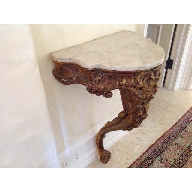 A French 19th c. Console table featuring a Demi-lune marble top above an elaborately carved giltwood base featuring a...