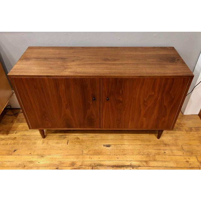Newly re-finished Walnut Credenza/Cabinet with two piano-hinged doors and black knobs. Tapered walnut legs. Inside there...