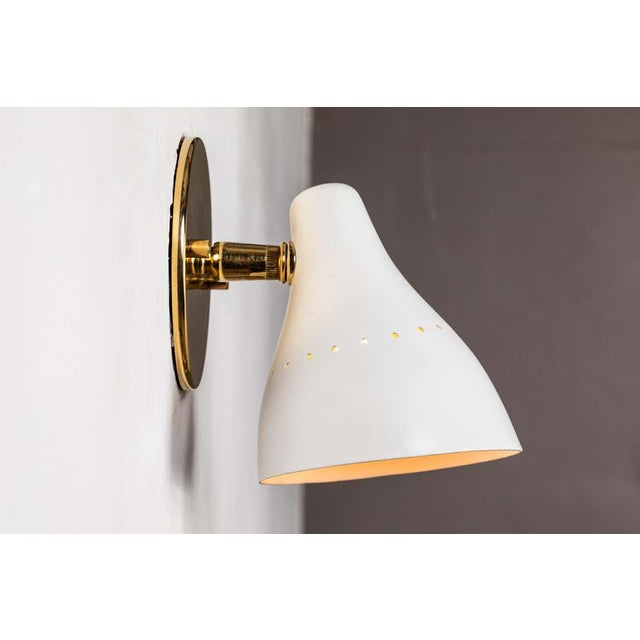 1950s Gino Sarfatti white articulating sconce for Arteluce. Executed in black painted perforated metal and brass. The...