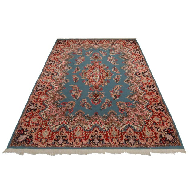 This is a vintage hand knotted wool Persian Kerman rug with rich colors and a floral motif throughout.