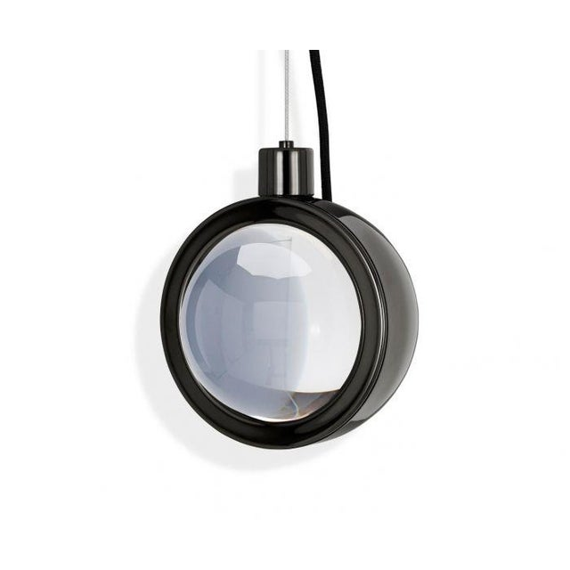 Framed in a glossy black plated stainless-steel surround, Spot Pendant is a massively thick glass lens designed to refract...