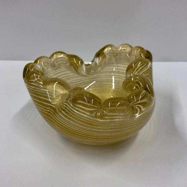 Gorgeous sculptural Murano glass dish featuring gold flecks throughout with accenting white pinstripes. Perfect addition...