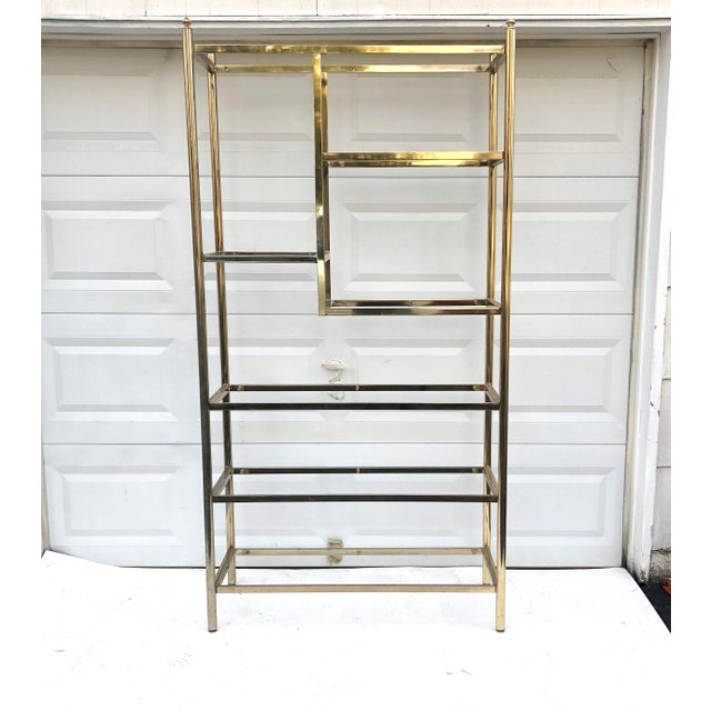 This stylish vintage modern brass and glass etagere makes an excellent display piece for home or business storage....