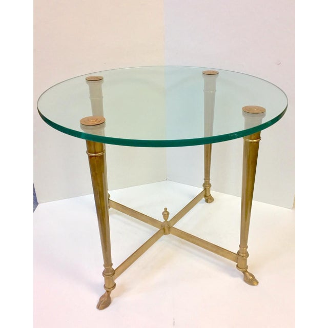 Beautiful side table in the style of Maison Jensen. Glass circular top with brass capped legs, securing the tabletop....