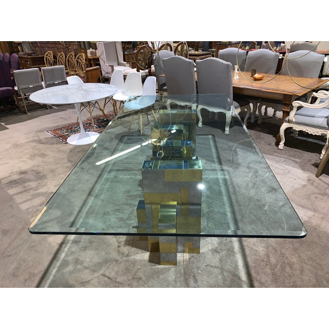A chrome and brass steel dining table with a large cityscape base supporting a glass top.
