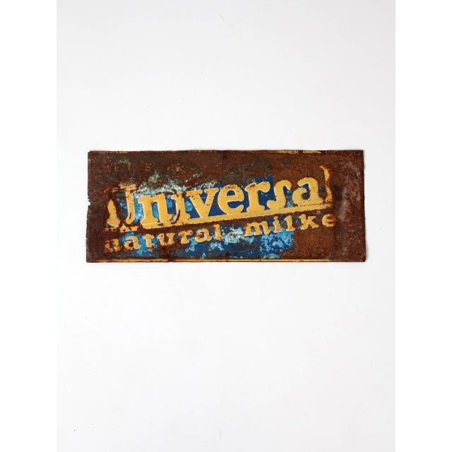 "A vintage ""Universal Natural Milker"" metal sign. With lots of character, the aged metal sign features the embossed company..."
