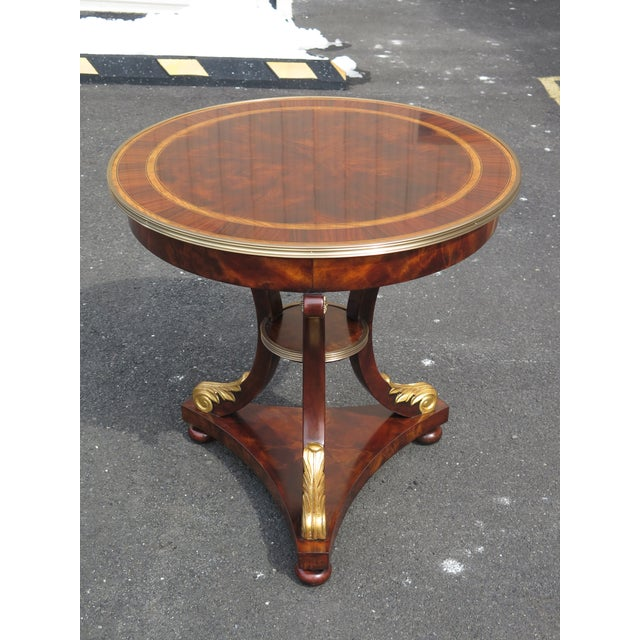 Theodore Alexander Althorp #50174 round mahogany occasional table. Features gorgeous figural mahogany top, brass trim work...