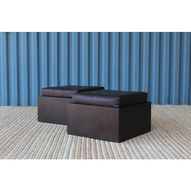 Pair of 1970s leather wrapped ottomans on rolling casters with removable cushions.