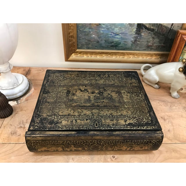 A 19th century chinoiserie black lacquer box in the form of a book with a fitted interior and velvet lined top.