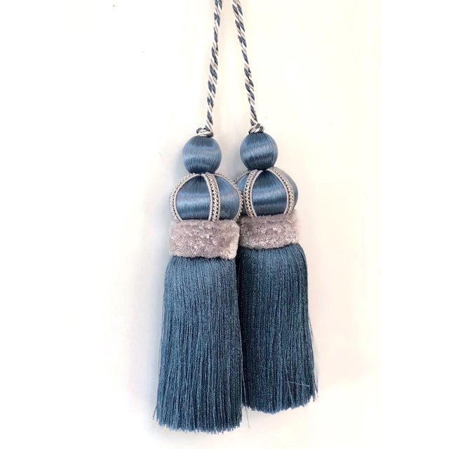 Pair of blue key tassels. Each tassel is connected by a twisted cord that loops over the top. A wood mold is covered with...