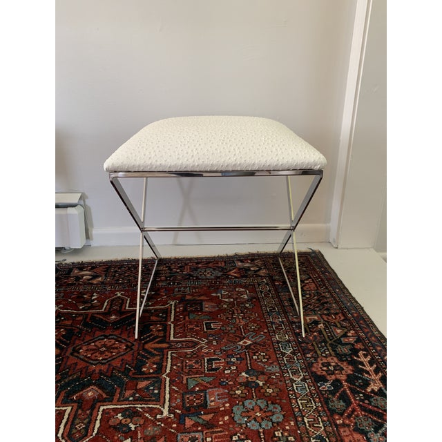 """A chic and modern piece, this """"X""""-framed stool is ahead of the trends with its metal sides and plush upholstered seat...."""
