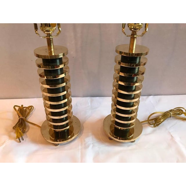A pair of brass and metal disk shaped Mid-Century Modern table lamps. This listing is for one of three sets of brass disk...