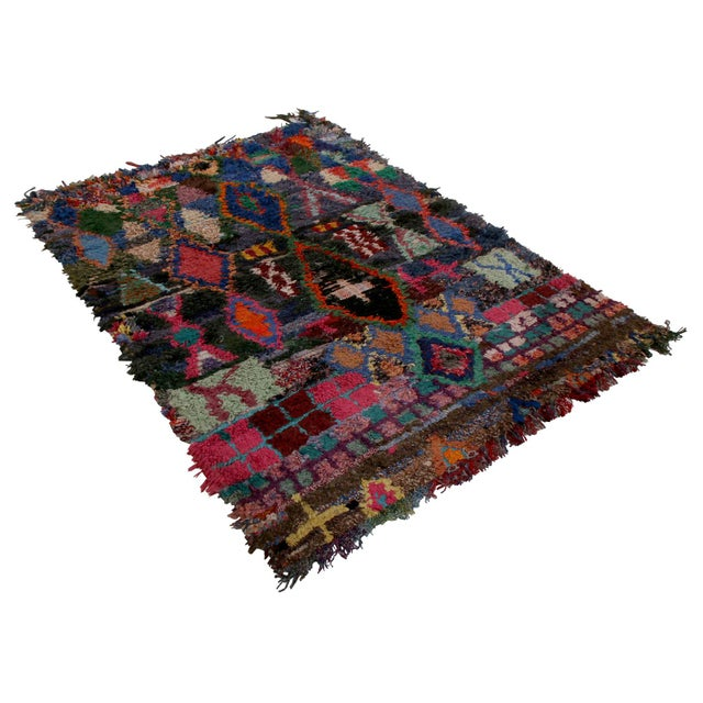 Hand knotted in textural, durable fabric originating between 1950-1960, this vintage Moroccan Berber rug enjoys one of the...