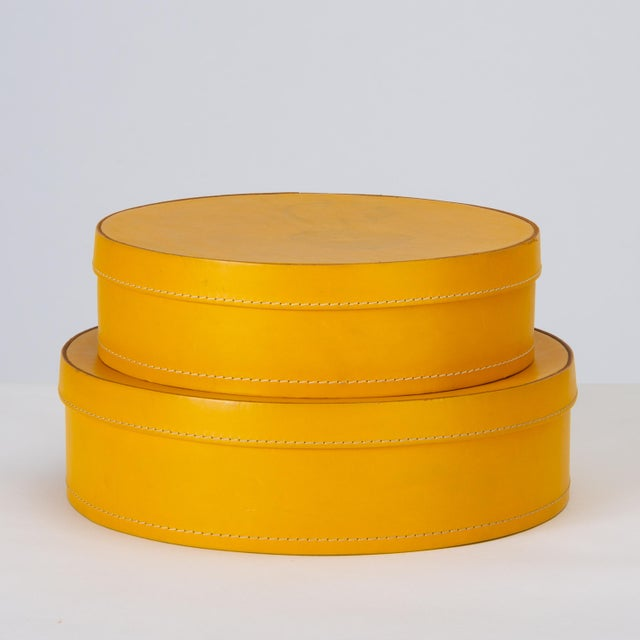 "A pair of round nesting boxes in mustard-colored leather by Italian company Arte Cuoio e Triangolo. The ""1980"" design..."