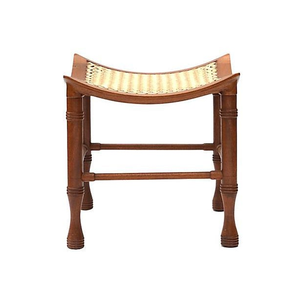 Egyptian Revival Thebes stool attributed to Liberty and Co. Made of stained beech wood with curved seat frame supporting...